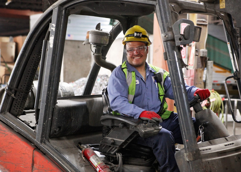 Eureka staffer in hard hat smiling while driving a piece of machinery in the facility.