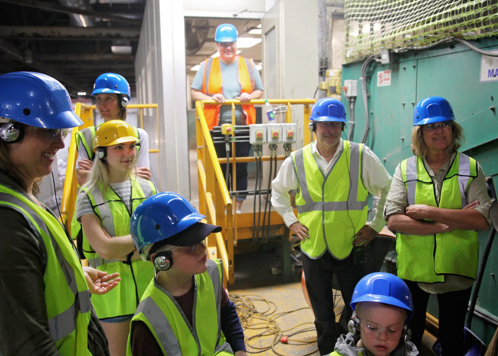 People in hard hats and reflective vests listen on a tour of Eureka's recycling facility.
