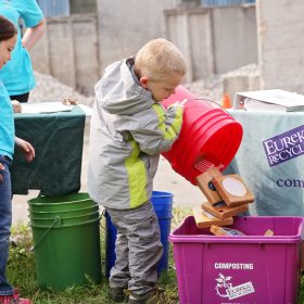 Children pouring discarded items into a compost bin.
