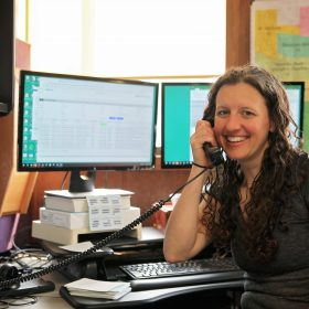 Eureka staffer smiling while answering the phone.