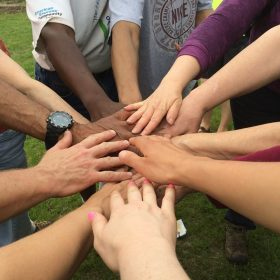 Group of people holds hands in middle of a circle.