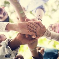 Image from below of young people joining hands in a circle.