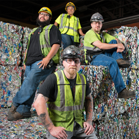 Group of Eureka staffers pose by blocks of compressed waste.
