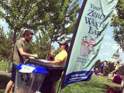 Volunteers stand by waste bins at event.
